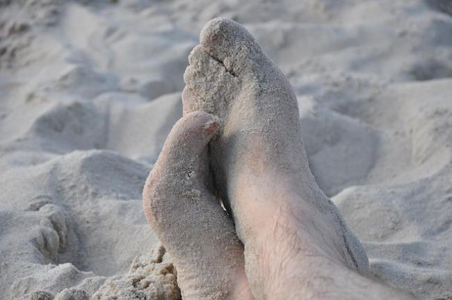 pies manchados de arena en la playa